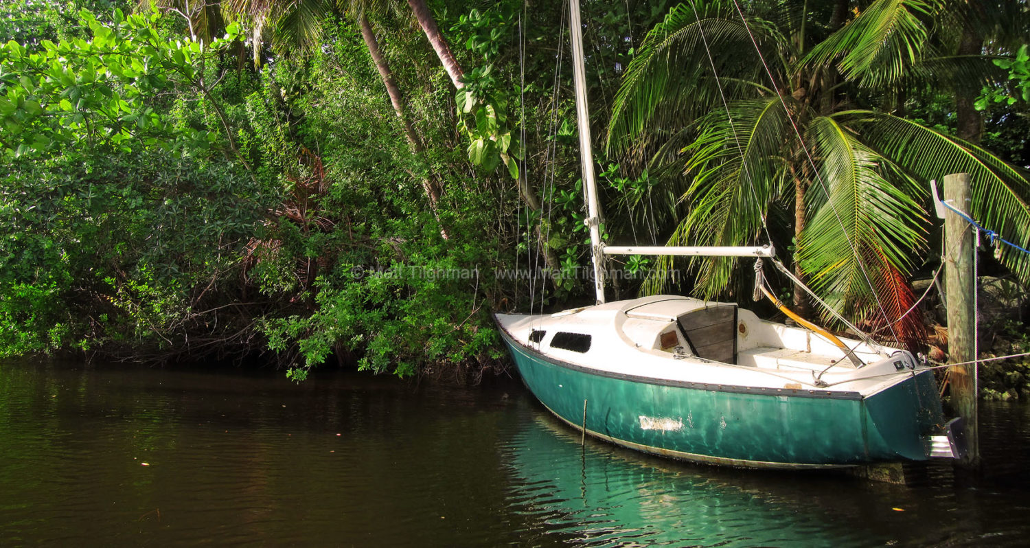 Fine art stock photograph of old derelict sailboat in Florida jungle. A once-loved sailboat sits idly decaying in the forests along Fort Lauderdale's New River.