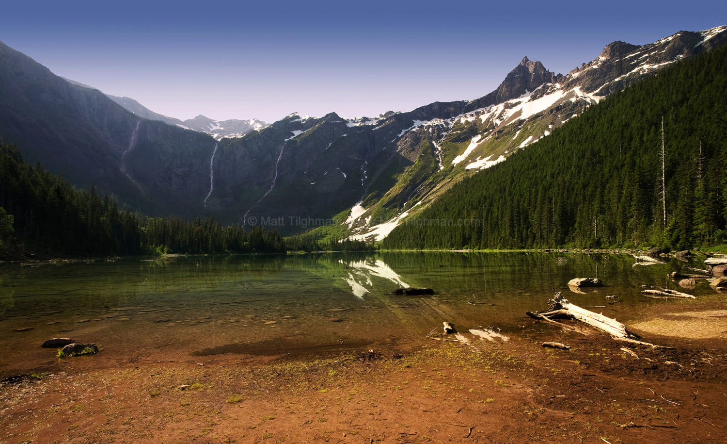 Fine art stock photograph of Avalanche Lake at dawn, flanked by towering mountains and boundless cascades fueled by snow melt. Glacier National Park, Montana.