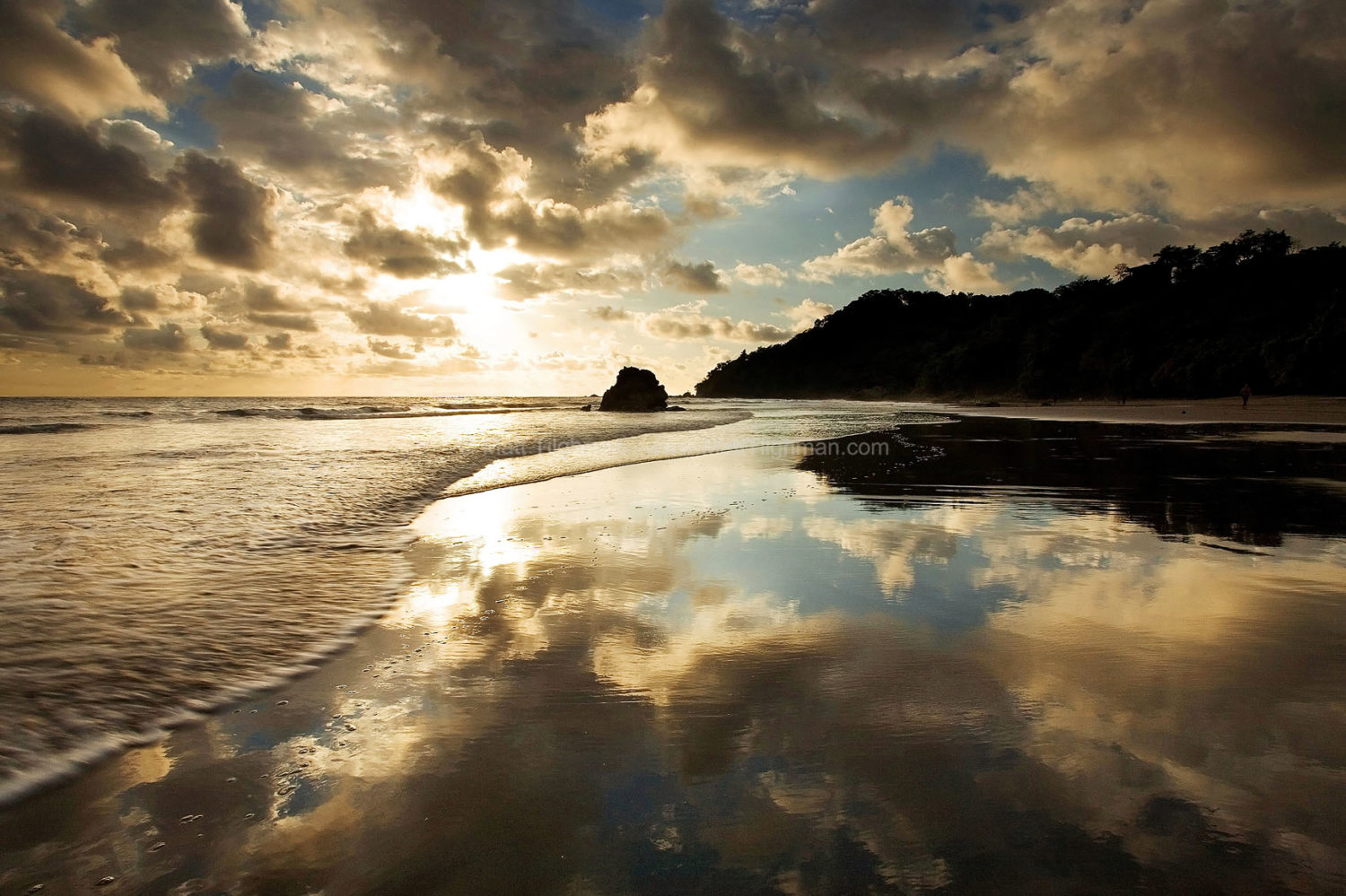 Fine art stock photograph from Manuel Antonio Park, Costa Rica. The sunset becomes reflected perfectly by the thin film of water left on the sand as the waves retreat.