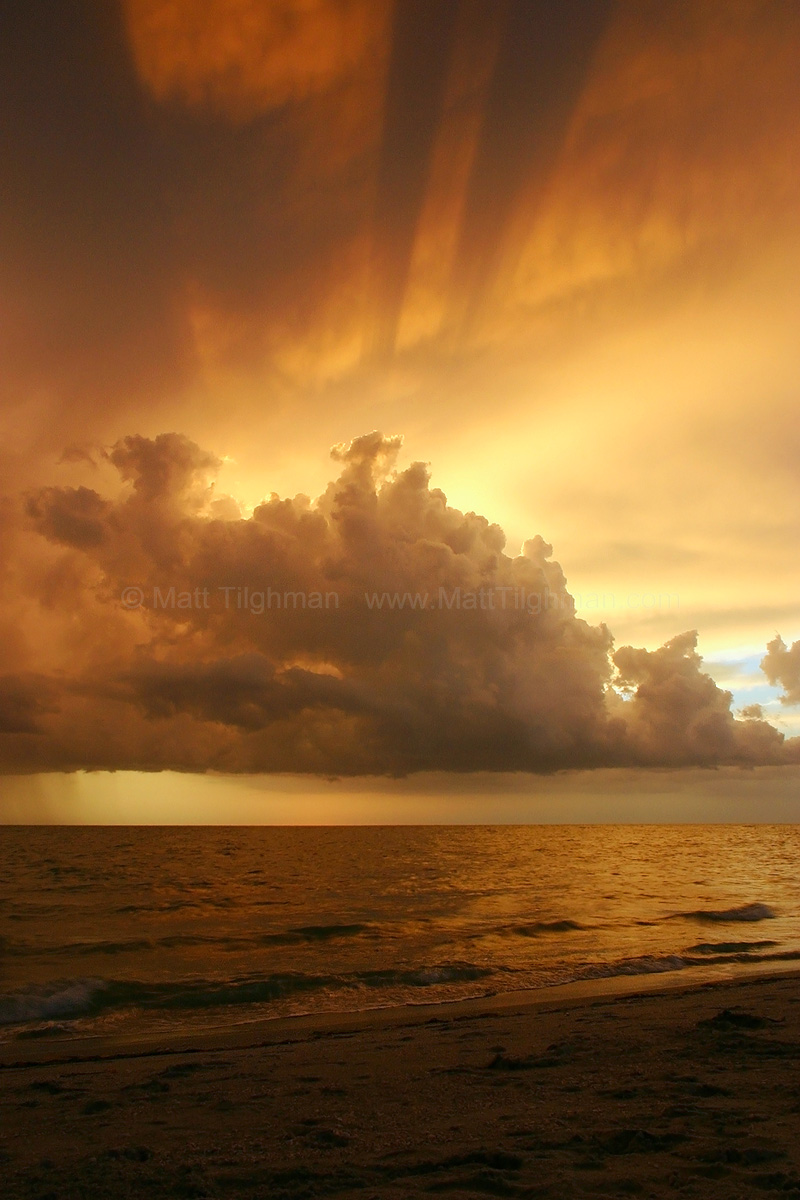 Fine art stock photograph of a stormy gulf coast sunset, as seen from Captiva, Florida. A giant storm passed through earlier, and left just enough of a crack for the sunshine to sneak through.