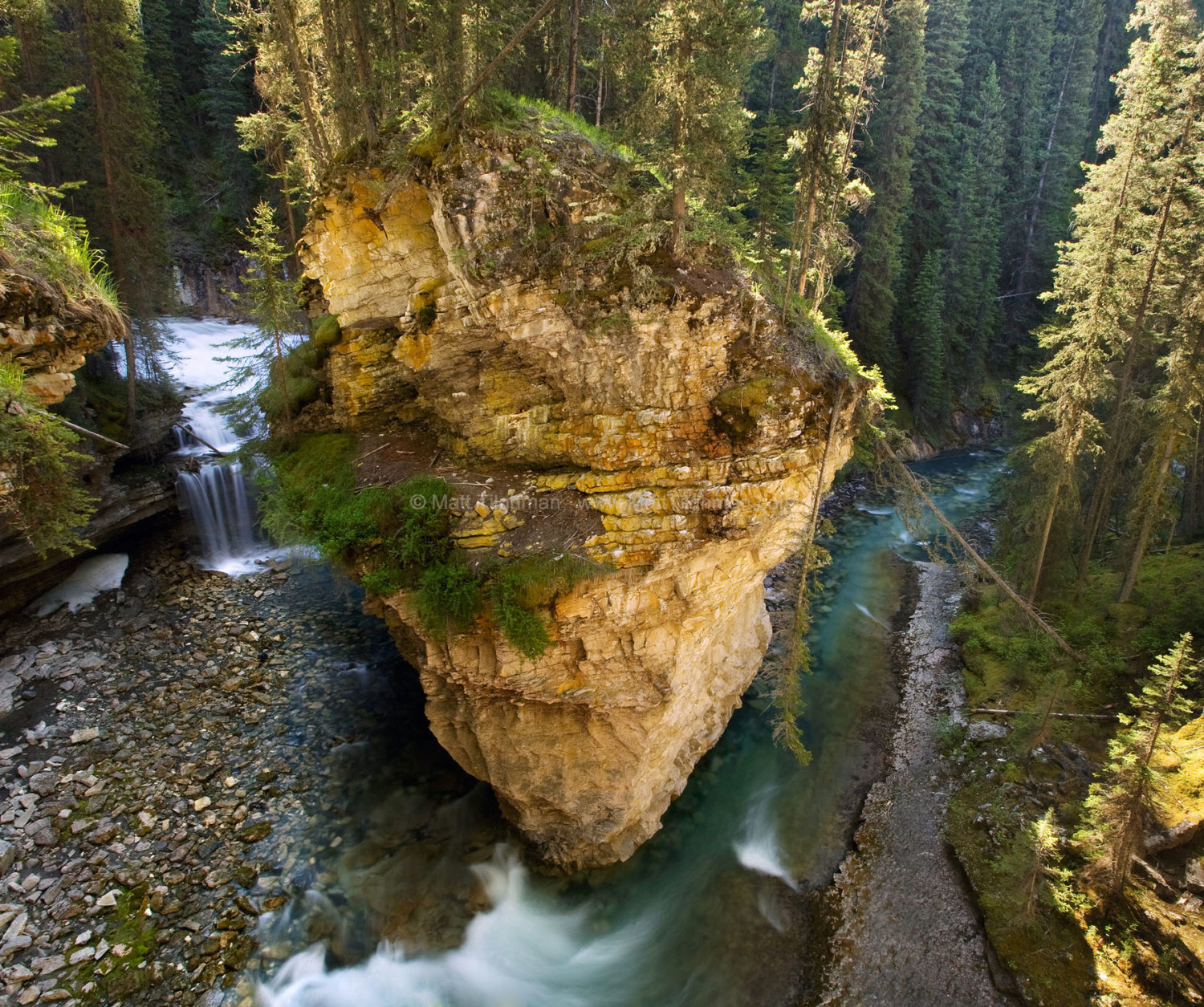 Fine art stock photograph of Johnston Canyon, in Canada's Banff National Park. A river bends around jagged moutain terrain.