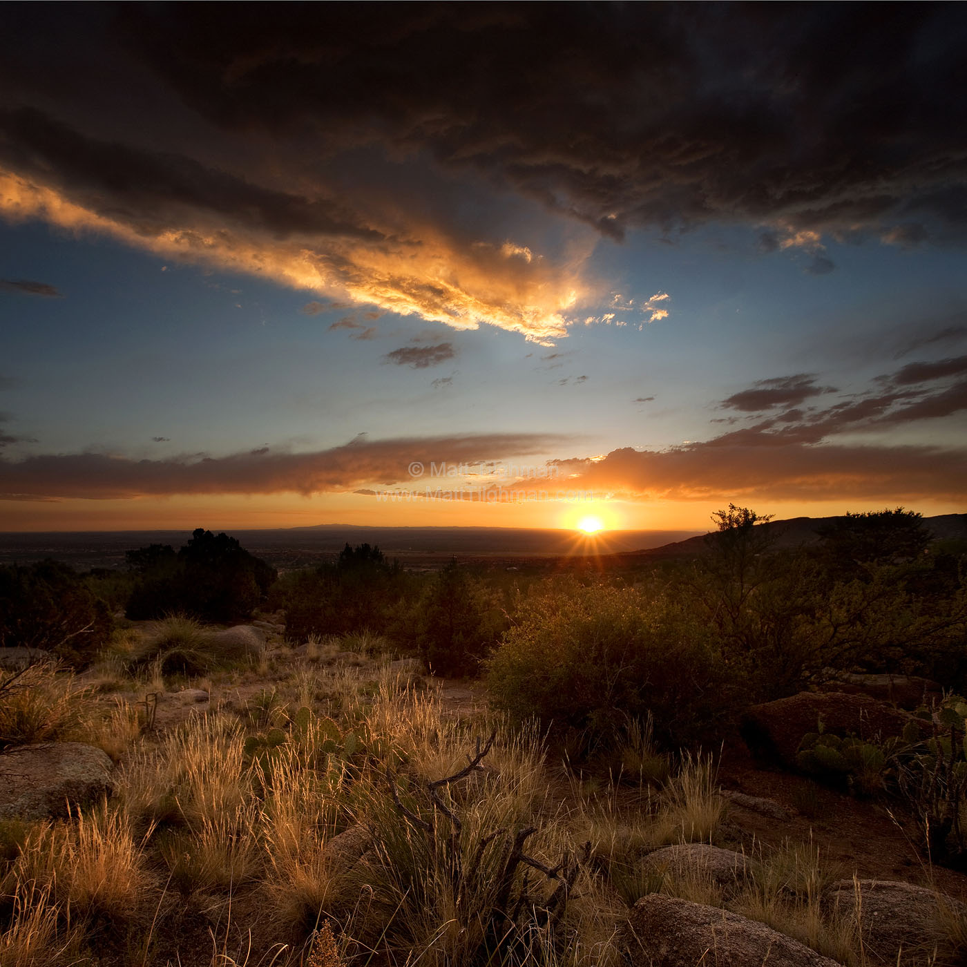 Fine art stock photograph of a volatile desert sunset outside of Albuquerque, New Mexico, near the Sandia Mountains. The summer monsoon season fills the sky with beautiful dramatic cloudscapes.