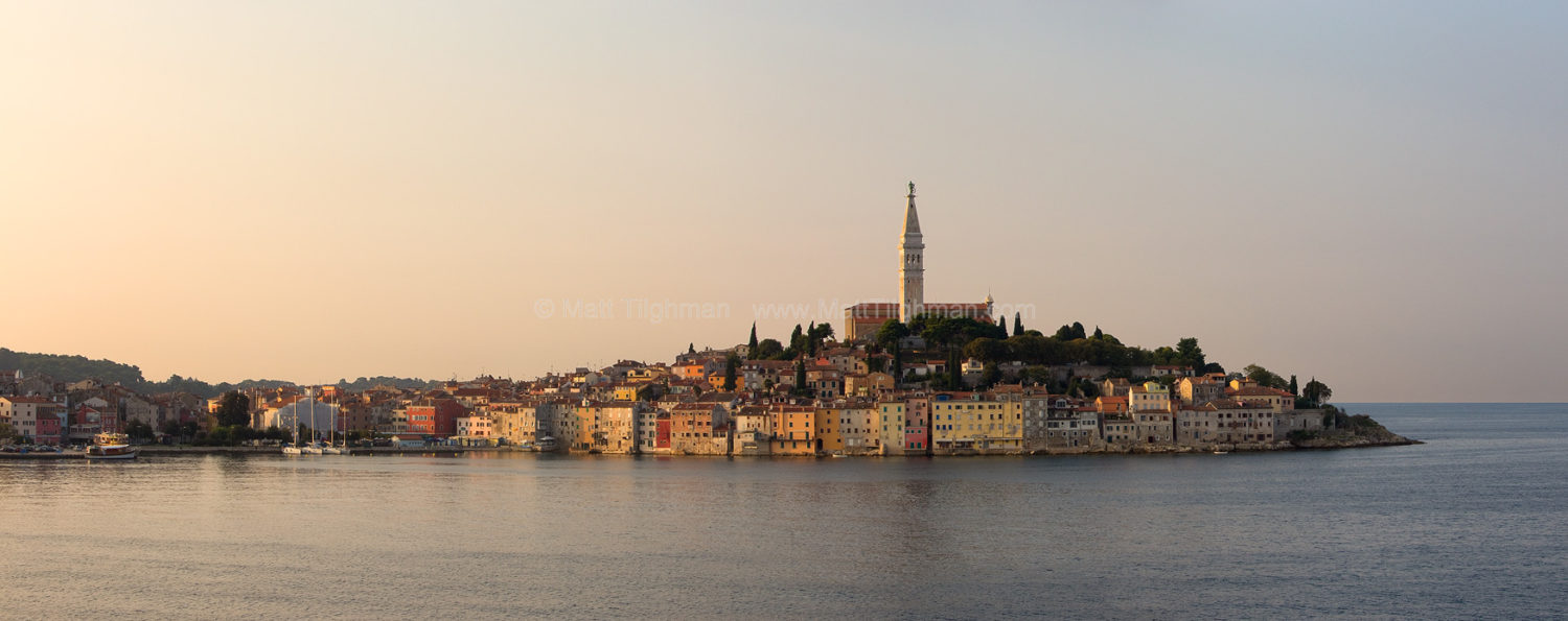 Fine art stock photograph of the beautiful waterfront of Rovinj Croatia at dawn, in Istria, with the Church of Saint Euphemia atop the hill.