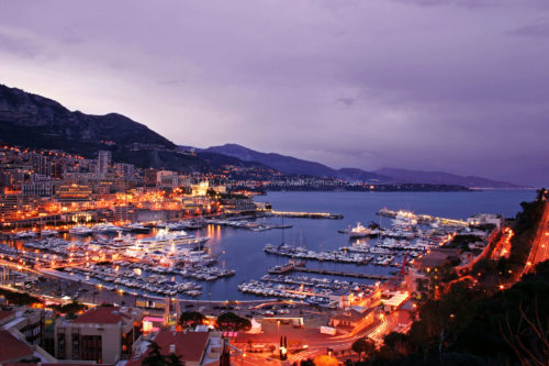 Fine art stock photo of Monte Carlo, Monaco, and the French Riviera. At twilight, the city begins to glimmer while the sea remains blue.