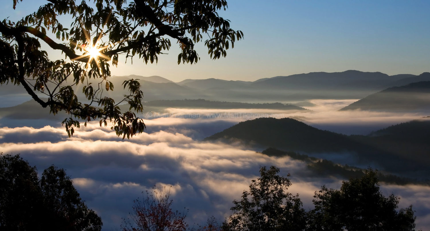 Fine art stock photograph of sunrise over the Smoky Mountains, near Santeetlah Gap. The fog keeps the forest compounds underneath, leading to a beautifully clear sky above.