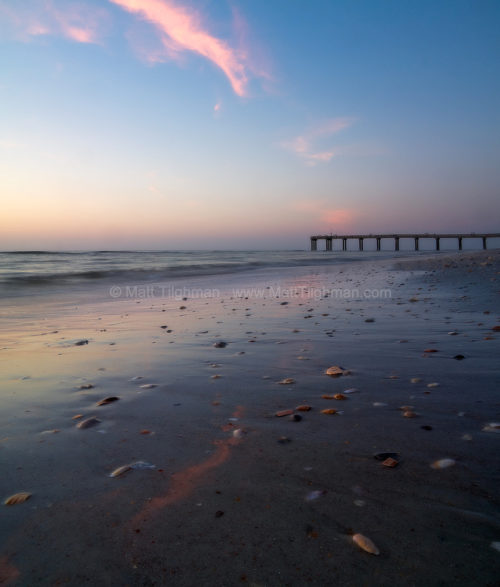 Fine art stock landscape photograph of sea shells and the Ocean Pier at sunrise, along Florida's St Augustine beach.