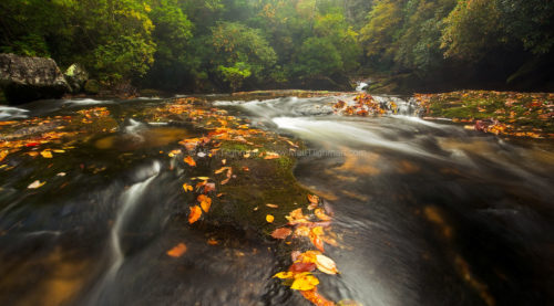 Fine art stock landscape photograph from the Chattooga River of North Carolina. Pictured here is the small waterfall Corkscrew Falls in Autumn.