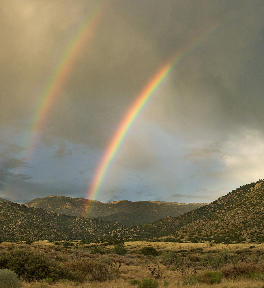 Fine art stock landscape photograph from outside Albuquerque, New Mexico. A desert double rainbow is the result of a summer monsoon over the Sandia Mountains.