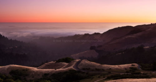 Fine art stock landscape photograph from California. Pacific Ocean fog laps at the coastal Santa Cruz Mountains, as a purple twilight settles in above.