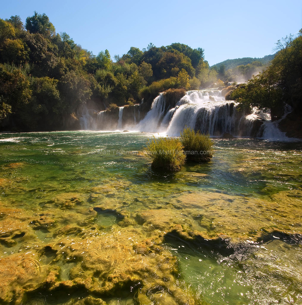 Fine art stock landscape photograph from Krka National Park, Croatia. The tufa rock formations shine brilliantly under the crystal clear alpine water.