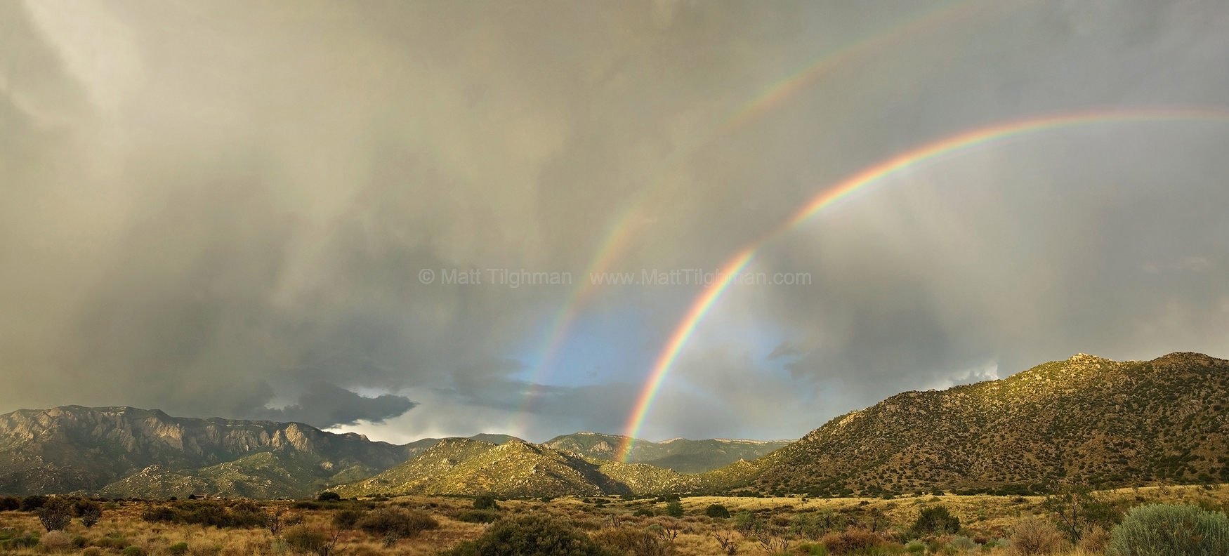 """Fine art stock landscape photograph from Albuquerque, New Mexico. A double rainbow over the Sandia Mountains proves the state's motto, """"Land of Enchantment."""""""