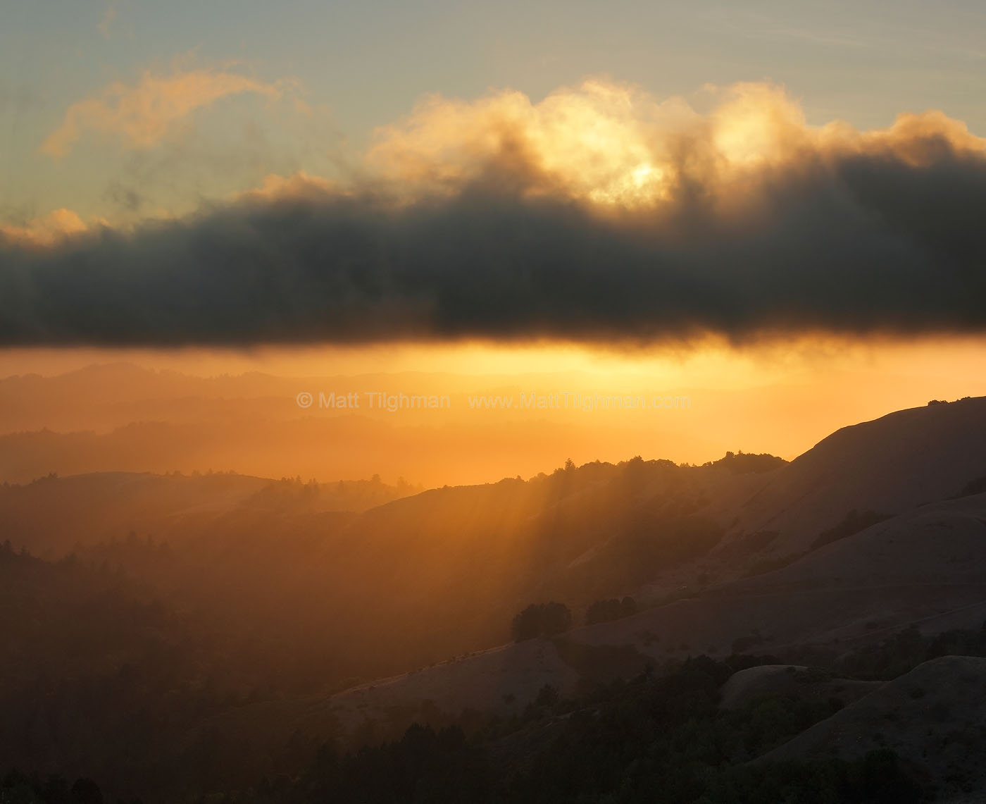 Fine art stock landscape photograph from Russian Ridge Open Space, California. Sunset rays get underneath the fog and light up the Santa Cruz Mountains