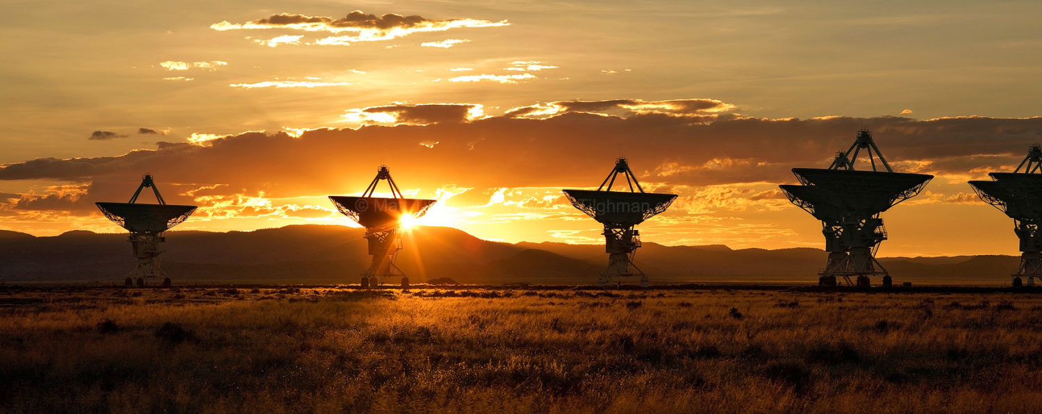 Fine art stock photograph of the Very Large Array at sunset. The clouds and mountains in the distance provide a stunning backdrop for the massive radio telescope.
