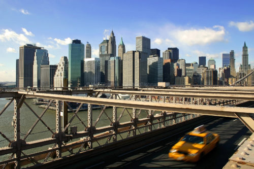 Fine art stock photograph of the famous New York City skyline, specifically downtown Manhattan, as seen from the Brooklyn Bridge. An iconic taxi cab passes by.