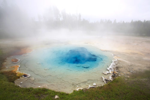 Fine art stock photograph from Yellowstone National Park. Warm air rising off the beautiful turquoise waters shrouds the thermal spring in dense mist.