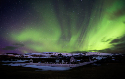 Fine art stock photograph of the Aurora Borealis in Iceland's night sky, above the small church and graveyard in the town of Hvammstangi.
