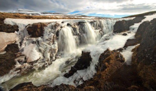 Fine art stock photograph of Kolufossar Waterfall, in Iceland's Kolugljúfur Canyon. As winter moves to spring, torrents of snow melt cascade into the canyon.