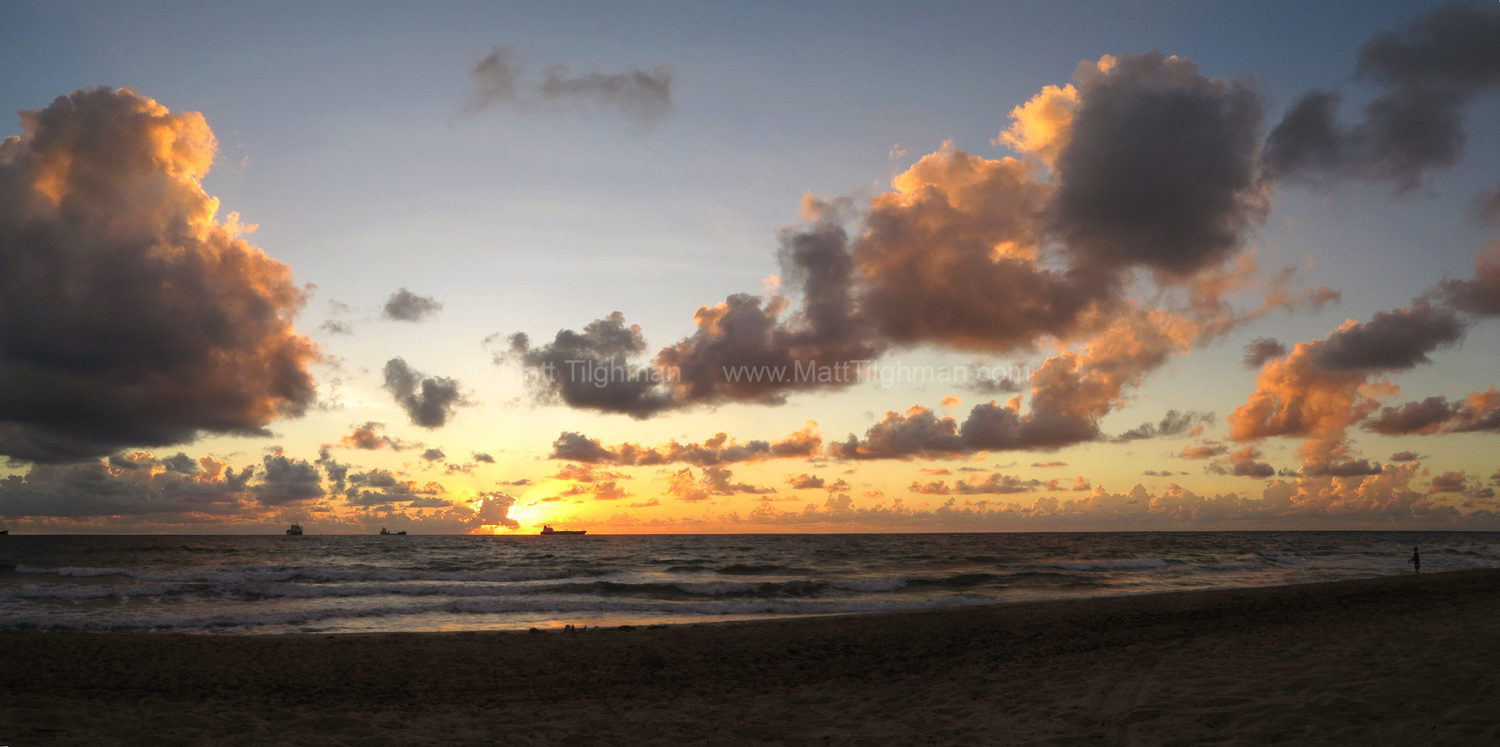 Fine art stock photograph of Las Olas Beach, in Fort Lauderdale, Florida, at dawn. The beautiful sunrise lights up the Atlantic Ocean gold and pink.