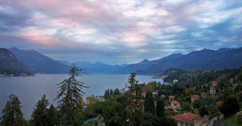 Fine art stock photograph of Lake Como at dawn. The dramatic mountains of Lombardy steeply descend down to the tranquil lake, under a cotton candy sunrise.
