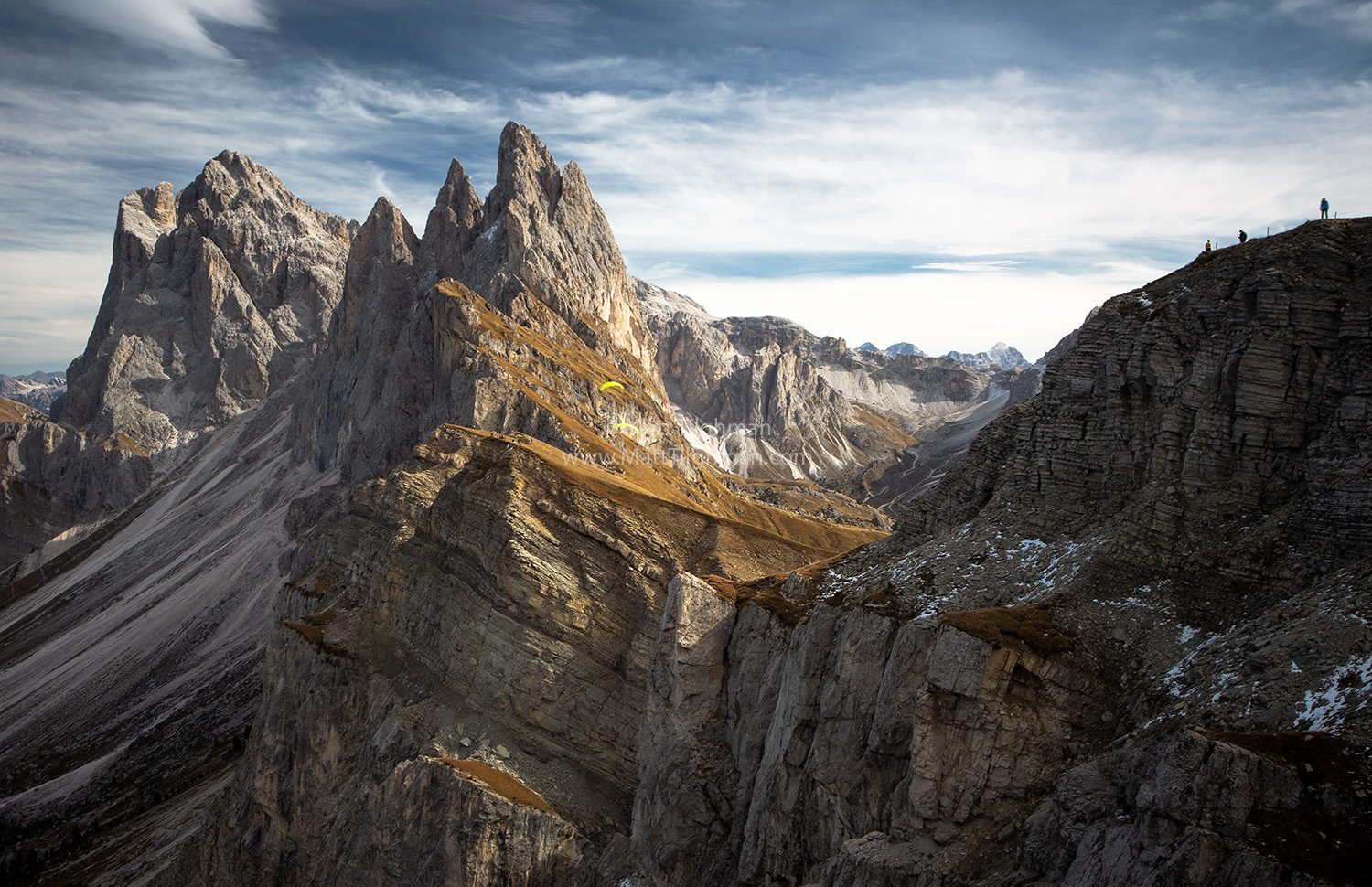 Fine art photograph of Seceda Mountain in the Italian Dolomites. Celebrating the end of tourist season, three locals take their paragliders to the sky.